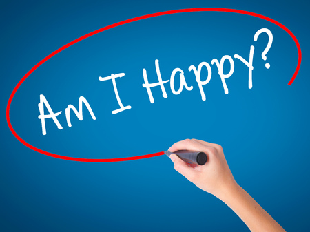 Women Hand writing Am I Happy? with black marker on visual screen. Isolated on blue. Business, technology, internet concept. Stock Photo
