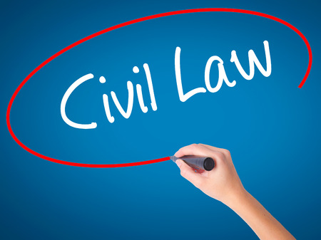 Women Hand writing Civil Law with black marker on visual screen. Isolated on blue. Business, technology, internet concept.