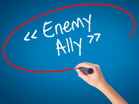 interdependence: Women Hand writing Enemy - Ally with black marker on visual screen. Isolated on blue. Business, technology, internet concept. Stock Photo