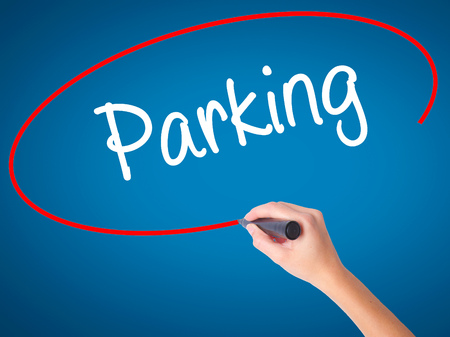 valet: Women Hand writing Parking with black marker on visual screen. Isolated on blue. Business, technology, internet concept. Stock Photo