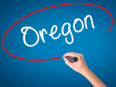 west river: Women Hand writing Oregon with black marker on visual screen. Isolated on blue. Business, technology, internet concept. Stock Photo