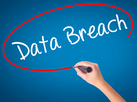 Women Hand writing Data Breach with black marker on visual screen. Isolated on blue. Business, technology, internet concept. Stock Photo