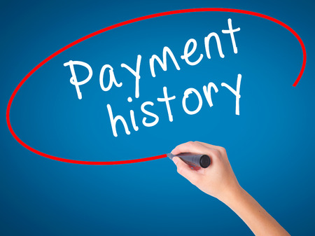 Women Hand writing Payment history with black marker on visual screen. Isolated on blue. Business, technology, internet concept. Stock Image