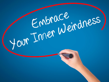 street wise: Women Hand writing Embrace Your Inner Weirdness  with black marker on visual screen. Isolated on blue. Business, technology, internet concept. Stock Photo