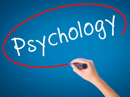 Women Hand writing Psychology with black marker on visual screen. Isolated on blue. Business, technology, internet concept. Stock Image Stock Photo