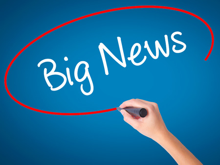 annoucement: Women Hand writing Big News with black marker on visual screen. Isolated on blue. Business, technology, internet concept. Stock Photo