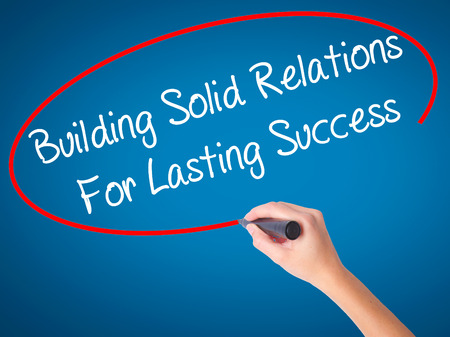 lasting: Women Hand writing Building Solid Relations For Lasting Success with black marker on visual screen. Isolated on blue. Business, technology, internet concept. Stock Image Stock Photo