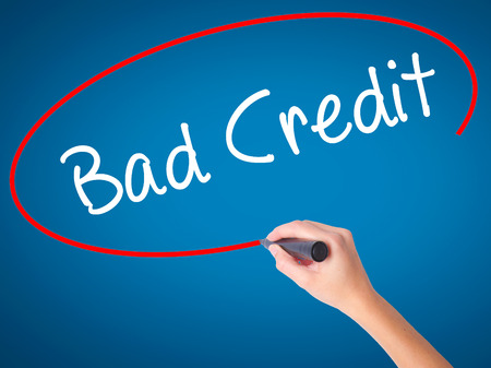 Women Hand writing Bad Credit with black marker on visual screen. Isolated on blue. Business, technology, internet concept. Stock Photo