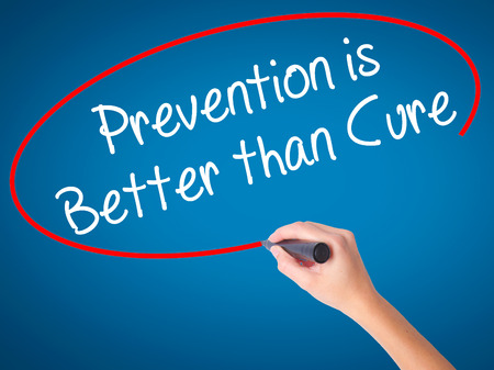 cure prevention: Women Hand writing Prevention is Better than Cure with black marker on visual screen. Isolated on blue. Business, technology, internet concept. Stock Photo Stock Photo