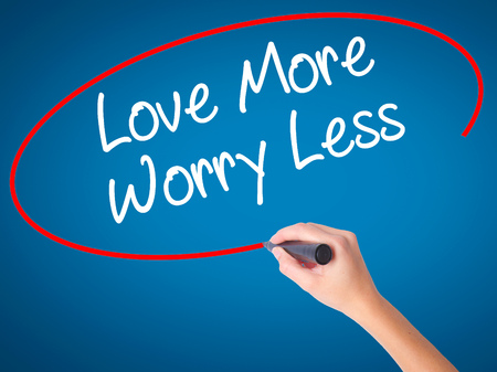 Women Hand writing Love More Worry Less with black marker on visual screen. Isolated on blue. Business, technology, internet concept. Stock Photo Stock Photo