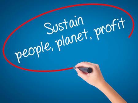 economic theory: Women Hand writing Sustain, people, planet, profit with black marker on visual screen. Isolated on blue. Business, technology, internet concept. Stock Photo