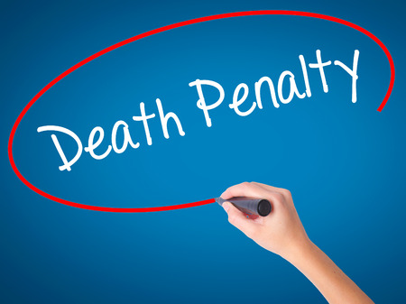 Women Hand writing Death Penalty with black marker on visual screen. Isolated on blue. Business, technology, internet concept. Stock Photo Stock Photo
