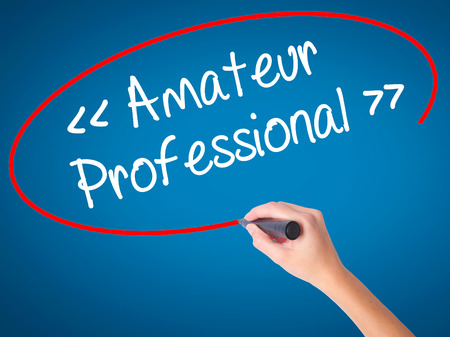 Women Hand writing Amateur - Professional with black marker on visual screen. Isolated on blue. Business, technology, internet concept. Stock  Photo