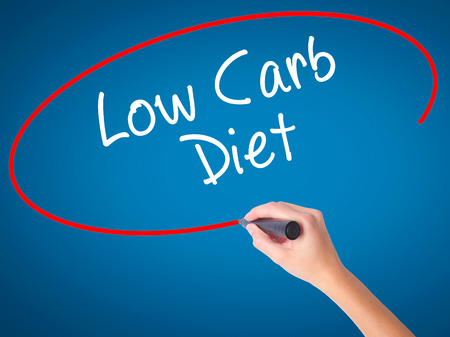 Women Hand writing Low Carb Diet with black marker on visual screen. Isolated on blue. Business, technology, internet concept. Stock Photo Stock Photo