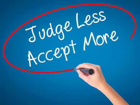 Women Hand writing Judge Less Accept More with black marker on visual screen. Isolated on blue. Business, technology, internet concept. Stock Photo Stock Photo