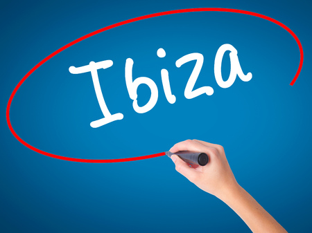 Women Hand writing Ibiza with black marker on visual screen. Isolated on blue. Travel, technology, internet concept. Stock Image