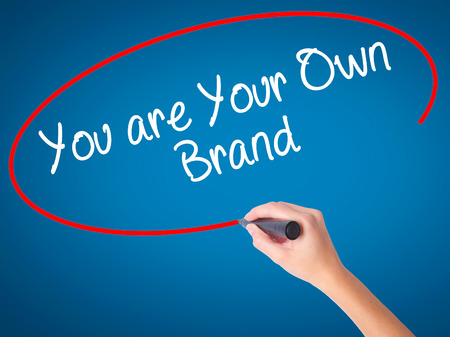 owning: Woman Hand writing You are Your Own Brand with black marker on visual screen. Isolated on white. Business, technology, internet concept. Stock Photo