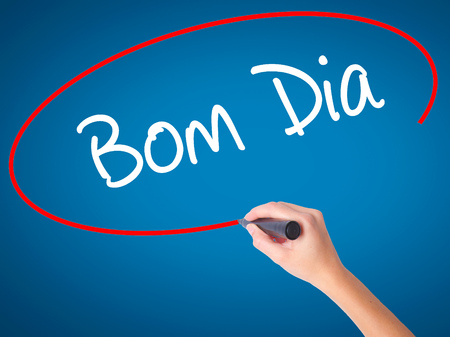 "Women Hand writing ""Bom Dia"" (In portuguese - Good Morning)  with black marker on visual screen. Isolated on blue. Business, technology, internet concept. Stock Photo"