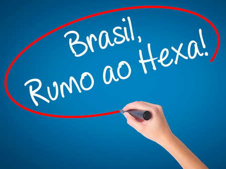 Women Hand writing Brasil, Rumo ao Hexa! with black marker on visual screen. Isolated on blue. Business, technology, internet concept. Stock Photo Stock Photo