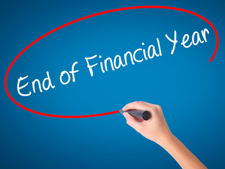 Women Hand writing End of Financial Year with black marker on visual screen. Isolated on blue. Business, technology, internet concept. Stock Photo