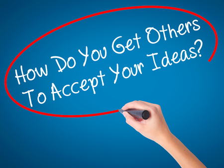 Women Hand writing How Do You Get Others To Accept Your Ideas? with black marker on visual screen. Isolated on blue. Business, technology, internet concept. Stock Photo