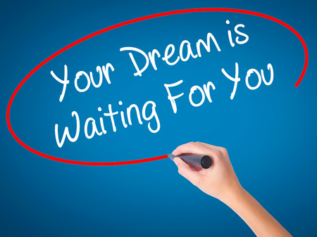 Woman Hand writing Your Dream is Waiting For You with black marker on visual screen. Isolated on background. Business, technology, internet concept. Stock Photo Stock Photo