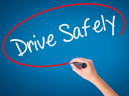 safely: Women Hand writing  Drive Safely with black marker on visual screen. Isolated on blue. Business, technology, internet concept. Stock Photo