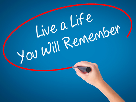 Women Hand writing Live a Life You Will Remember with black marker on visual screen. Isolated on blue. Business, technology, internet concept. Stock Photo