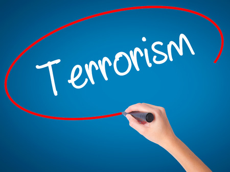 cyber terrorism: Women Hand writing Terrorism with black marker on visual screen. Isolated on blue. Business, technology, internet concept. Stock Photo