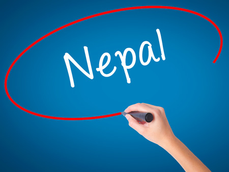 Women Hand writing Nepal  with black marker on visual screen. Isolated on blue. Business, technology, internet concept. Stock Photo