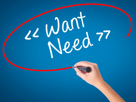necessity: Women Hand writing Want - Need  with black marker on visual screen. Isolated on blue. Business, technology, internet concept. Stock Photo