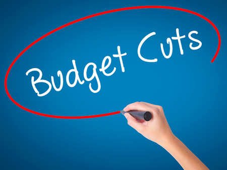 Women Hand writing Budget Cuts with black marker on visual screen. Isolated on blue. Business, technology, internet concept. Stock Photo Stock Photo
