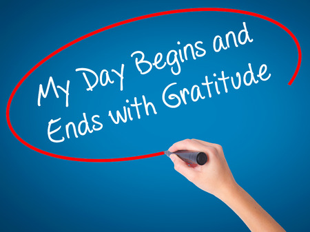 begins: Women Hand writing My Day Begins and Ends with Gratitude with black marker on visual screen. Isolated on blue. Business, technology, internet concept. Stock Photo