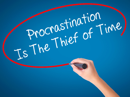 Women Hand writing  Procrastination Is The Thief of Time with black marker on visual screen. Isolated on blue. Business, technology, internet concept. Stock Image