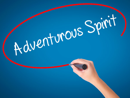 Women Hand writing Adventurous Spirit with black marker on visual screen. Isolated on blue. Business, technology, internet concept. Stock Photo