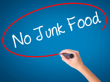 Women Hand writing No Junk Food with black marker on visual screen. Isolated on blue. Business, technology, internet concept. Stock Photo Stock Photo