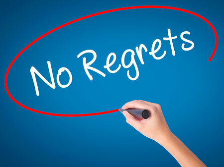 Women Hand writing No Regrets with black marker on visual screen. Isolated on blue. Business, technology, internet concept. Stock Photo Stock Photo