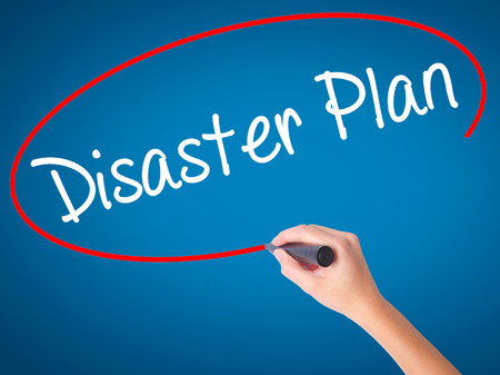 Women Hand writing Disaster Plan with black marker on visual screen. Isolated on blue. Business, technology, internet concept. Stock Photo Stock Photo