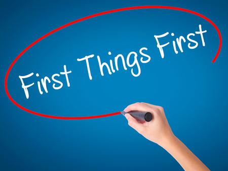 Women Hand writing First Things First with black marker on visual screen. Isolated on blue. Business, technology, internet concept. Stock Photo