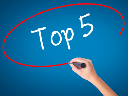 Women Hand writing Top 5 with black marker on visual screen. Isolated on blue. Business, technology, internet concept. Stock Photo