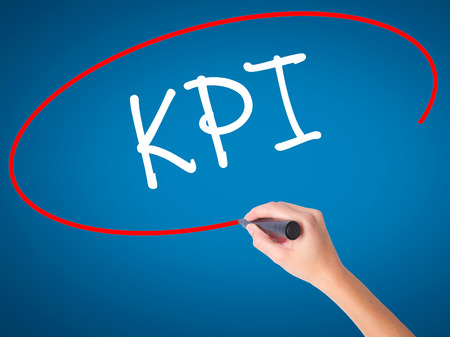 Women Hand writing KPI (Key Performance Indicator) with black marker on visual screen. Isolated on blue. Business, technology, internet concept. Stock Photo