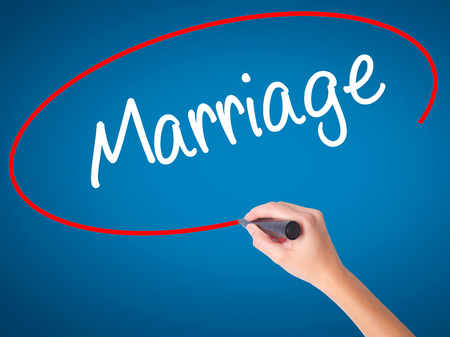 Women Hand writing Marriage with black marker on visual screen. Isolated on blue. Business, technology, internet concept. Stock Photo