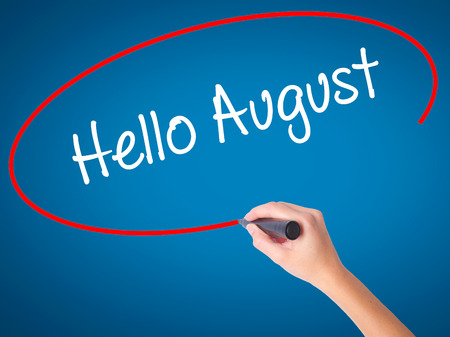 Women Hand writing Hello August with black marker on visual screen. Isolated on blue. Business, technology, internet concept. Stock Photo