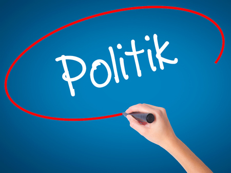Women Hand writing Politik (Politics in German) with black marker on visual screen. Isolated on blue. Business, technology, internet concept. Stock Photo