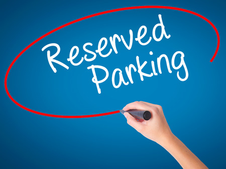 valet: Women Hand writing Reserved Parking with black marker on visual screen. Isolated on blue. Business, technology, internet concept. Stock Photo Stock Photo