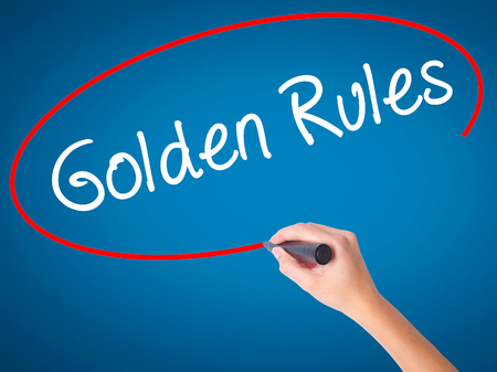 golden rule: Women Hand writing Golden Rules with black marker on visual screen. Isolated on blue. Business, technology, internet concept. Stock Photo Stock Photo
