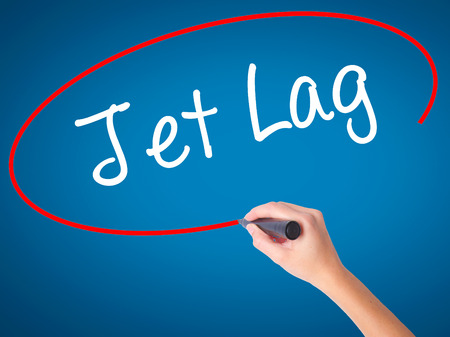 Women Hand writing  Jet Lag with black marker on visual screen. Isolated on blue. Business, technology, internet concept. Stock Photo
