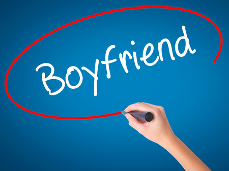 Women Hand writing Boyfriend with black marker on visual screen. Isolated on blue. Business, technology, internet concept. Stock Photo