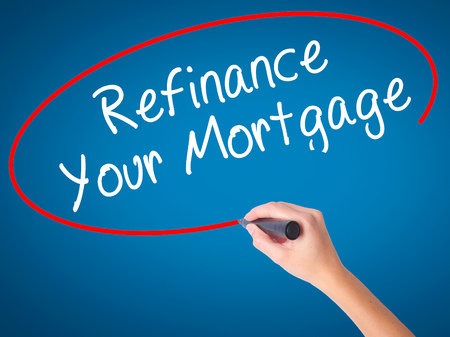 Women Hand writing Refinance Your Mortgage with black marker on visual screen. Isolated on blue. Business, technology, internet concept. Stock Image