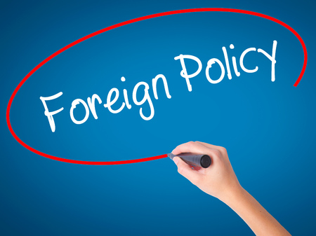 Women Hand writing Foreign Policy with black marker on visual screen. Isolated on blue. Business, technology, internet concept. Stock Photo Stock Photo